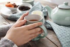 Mujer con la taza de té delicioso en la tabla imagenes de archivo