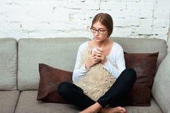 Mujer con la taza de té en el sofá Imagen de archivo