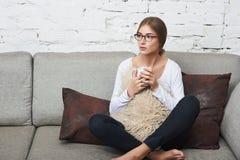 Mujer con la taza de té en el sofá Fotos de archivo