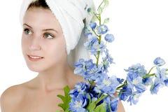 Mujer con la toalla alrededor de las flores de la explotación agrícola del pelo Imagenes de archivo