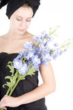 Mujer con la toalla alrededor de las flores de la explotación agrícola del pelo Fotografía de archivo libre de regalías