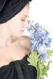 Mujer con la toalla alrededor de las flores de la explotación agrícola del pelo Foto de archivo libre de regalías