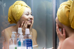 Mujer con la toalla en el espejo cercano principal Imagenes de archivo