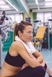 Mujer con la toalla que descansa en el gimnasio después de entrenar Imagen de archivo