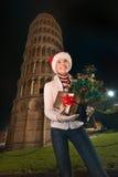 Mujer con la torre inclinada cercana de la caja del árbol de navidad y de regalo, Pisa Foto de archivo
