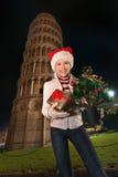 Mujer con la torre inclinada cercana de la caja del árbol de navidad y de regalo, Pisa Imagen de archivo