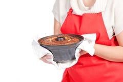 Mujer con la torta del bundt y el delantal rojo fotos de archivo