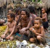 Mujer con la tribu de Dani de los niños que se sienta en la tierra en el pueblo Fotografía de archivo libre de regalías