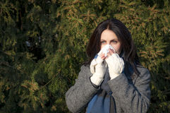 Mujer con las alergias que soplan su nariz Fotos de archivo libres de regalías