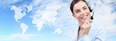 Mujer con las auriculares que sonríe, mapa del mundo del operador del servicio de atención al cliente Fotografía de archivo libre de regalías