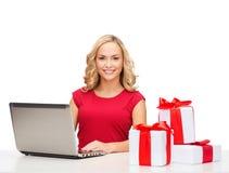 Mujer con las cajas y el ordenador portátil de regalo Foto de archivo libre de regalías