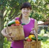 Mujer con las cestas de vehículos cosechados Imagen de archivo libre de regalías
