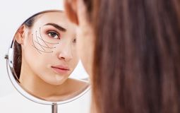 Mujer con las flechas de elevación en la cara que mira en el espejo Fotografía de archivo