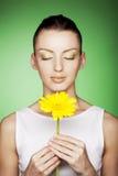 Mujer con las flores amarillas en fondo verde imágenes de archivo libres de regalías