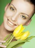 mujer con las flores amarillas en fondo verde Foto de archivo