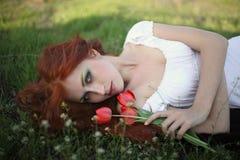 Mujer con las flores del tulipán Foto de archivo