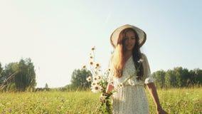 Mujer con las flores en el campo en la mañana almacen de metraje de vídeo