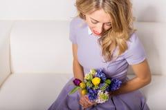 Mujer con las flores que se sientan en el sofá Imágenes de archivo libres de regalías