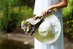 Mujer con las flores y el sombrero en manos Primer fotografía de archivo