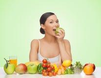 Mujer con las frutas y verduras que come la manzana foto de archivo