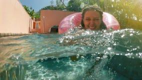 Mujer con las gafas de sol en el bikini azul que miente en flotador rosado inflable del buñuelo en piscina en día de verano solea almacen de video