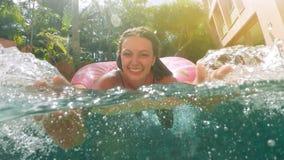 Mujer con las gafas de sol en el bikini azul que miente en flotador rosado inflable del buñuelo en piscina en día de verano solea metrajes