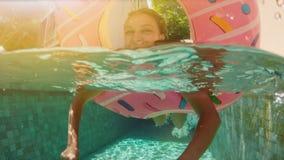 Mujer con las gafas de sol en el bikini azul que miente en flotador rosado inflable del buñuelo en piscina en día de verano solea almacen de metraje de vídeo