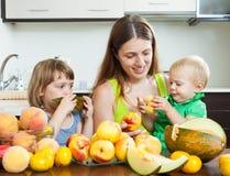 Mujer con las hijas con los melocotones Fotografía de archivo libre de regalías