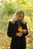 Mujer con las hojas de arce amarillas Foto de archivo libre de regalías