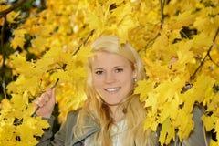 Mujer con las hojas de otoño Foto de archivo
