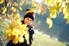 Mujer con las hojas del amarillo del arce Imágenes de archivo libres de regalías