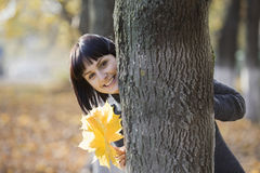 Mujer con las hojas otoñales detrás del árbol Fotografía de archivo libre de regalías