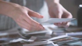 Mujer con las imágenes de transferencia inmediatas de la impresión en manos mirada de las fotos polaroid del viaje por carretera  metrajes