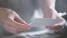 Mujer con las imágenes de transferencia inmediatas de la impresión en manos mirada de las fotos polaroid del viaje por carretera  almacen de video