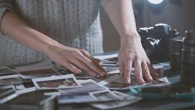 Mujer con las imágenes de transferencia inmediatas de la impresión en manos mirada de las fotos polaroid del viaje por carretera  almacen de metraje de vídeo