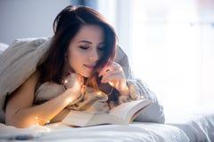 Mujer con las luces de hadas y el libro Imagen de archivo libre de regalías