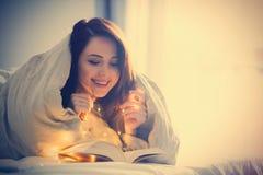 Mujer con las luces de hadas y el libro Imagenes de archivo