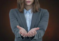 Mujer con las manos abiertas con el fondo marrón Imagen de archivo libre de regalías