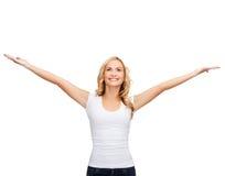 Mujer con las manos aumentadas en camiseta blanca en blanco Foto de archivo libre de regalías