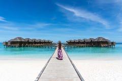Mujer con las manos aumentadas en el puente en la playa en Maldivas Foto de archivo libre de regalías