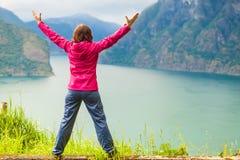 Mujer con las manos aumentadas en los fiordos noruegos de las montañas Imagen de archivo libre de regalías