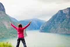 Mujer con las manos aumentadas en los fiordos noruegos de las montañas Imágenes de archivo libres de regalías