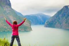 Mujer con las manos aumentadas en los fiordos noruegos de las montañas Fotos de archivo libres de regalías