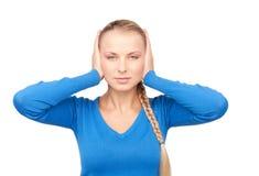 Mujer con las manos en los oídos Imagenes de archivo