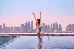 Mujer con las manos encima de disfrutar de la opinión de la mañana de la piscina del infinito del top del tejado en Asia imagenes de archivo