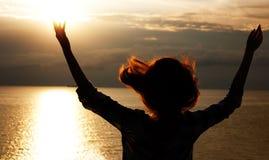 Mujer con las manos levantadas que miran al cielo tempestuoso Imagen de archivo libre de regalías