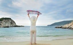 Mujer con las manos que detienen una bufanda en la playa Imagen de archivo libre de regalías