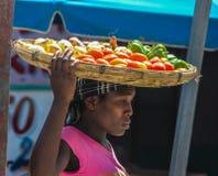 Mujer con las mercancías en cesta en la cabeza Foto de archivo libre de regalías