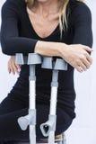 Mujer con las muletas Foto de archivo