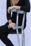 Mujer con las muletas Imagen de archivo
